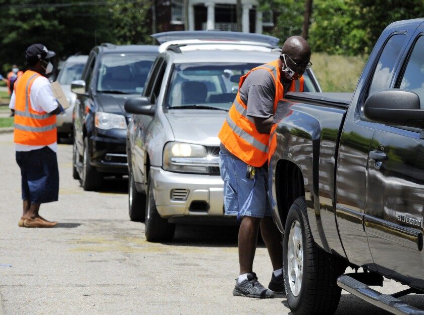Volunteers load boxes of fruit and produce into vehicles at a site where free food was distributed to residents of Alabama's Black Belt region in Selma, Ala., on Thursday, June 4, 2020. Relief groups are trying to provide aid during the pandemic in the mostly black, historically poor region, which has the state's highest unemployment and coronavirus infection rates. (AP Photo/Jay Reeves)