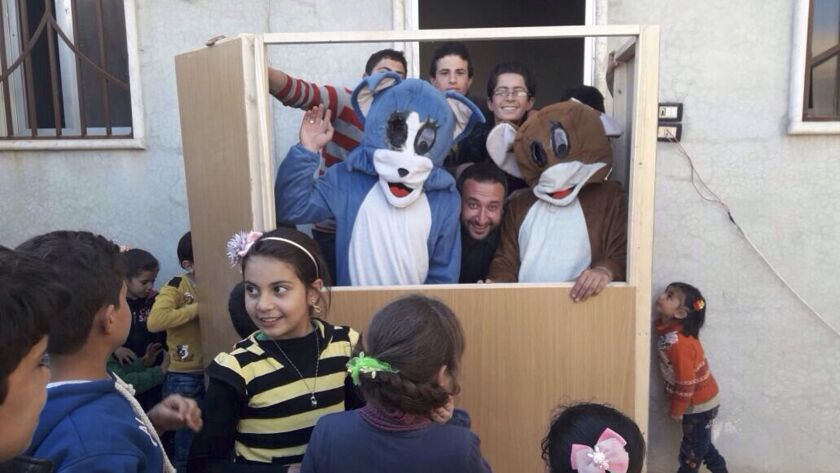 Ahmad Khatab (center) is flanked by performers dressed as cartoon cat and mouse duo Tom and Jerry at