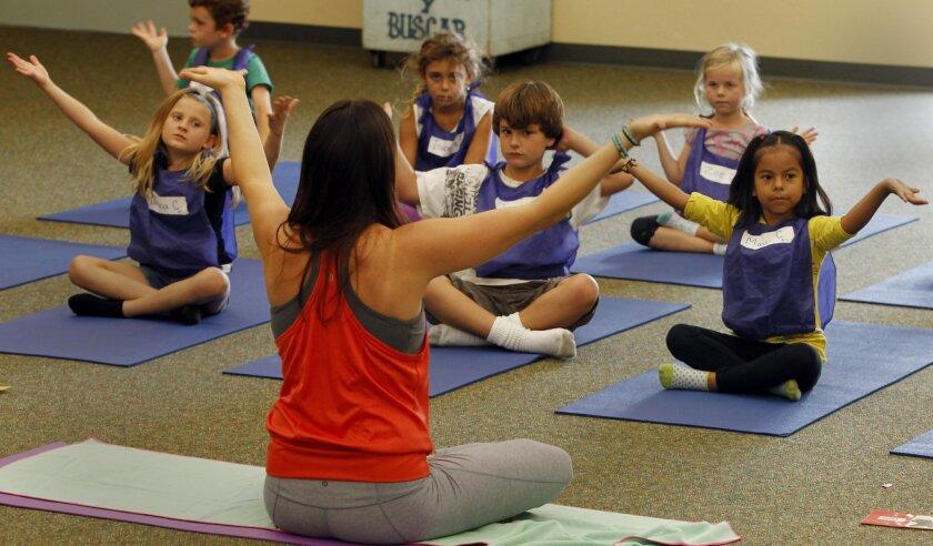 Yoga teacher Jackie Bergeron works with students at Paul Ecke Central Elementary School in Encinitas last October. / photo by Eduardo Contreras * U-T