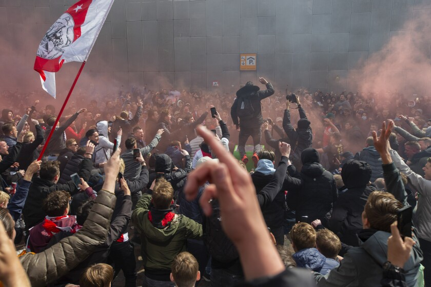 Ajax supporters celebrate outside the Arena as their team scored their second goal in the Dutch Eredivisie Premier League title during the soccer match between Ajax and Emmen at the Johan Cruyff ArenA in Amsterdam, Netherlands, Sunday, May 2, 2021. (AP Photo/Peter Dejong)