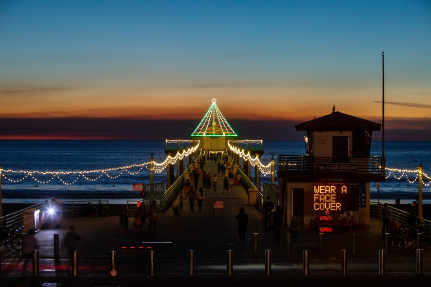 MANHATTAN BEACH, CA - DECEMBER 03: With annual holiday decorations on display, a city sign alerts visitors to the Pier in Manhattan Beach, CA, that face coverings are required, or face up to a $350 fine, on Thursday, Dec. 3, 2020. Due to increases in COVID-19 cases across Southern California, the city of Manhattan Beach is requiring anyone out in public to wear a face covering, or face fines. (Jay L. Clendenin / Los Angeles Times)
