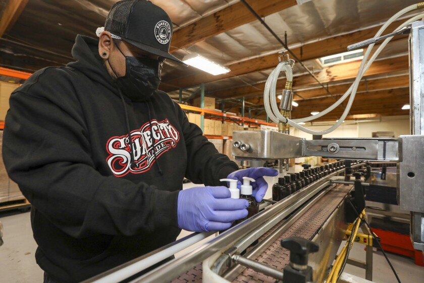 Eugene Cayetano caps bottles of hand sanitizers at the Santa Ana factory of Suavecito, which usually manufactures pomade and Chicano hipster fashion.