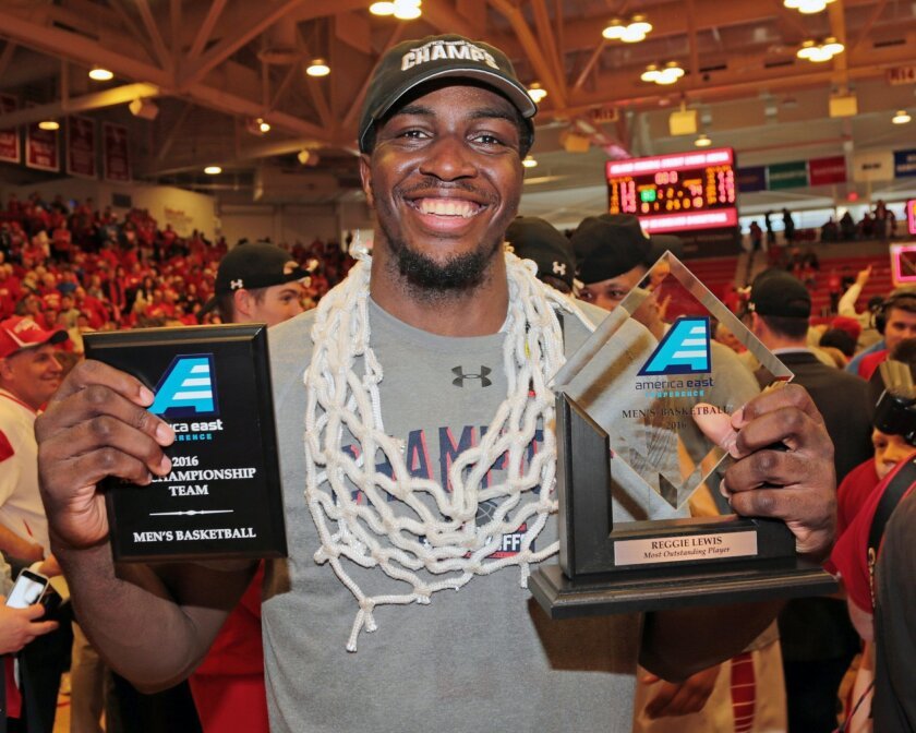 Stony Brook's Jameel Warney celebrates while wearing the net and displaying his MVP trophy celebrate following their 80-74 win over Vermont in an NCAA college basketball game in the championship of the  American East Conference men's tournament, Saturday, March 12, 2016, in Stony Brook, N.Y. (Danie