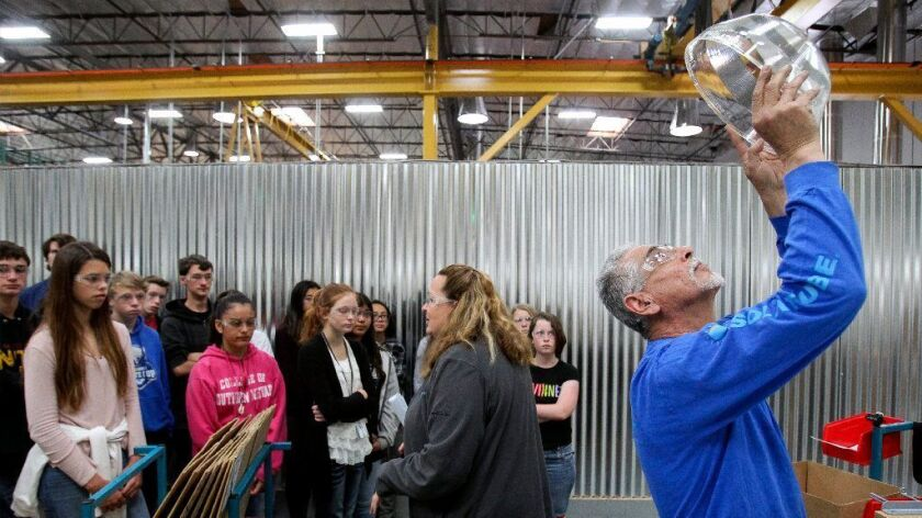 """Technician Cesar Perez inspects a clear plastic part for Solatube before packaging it as Purchasing Manager Shannon Cassidy, center, talks to a group of middle school students from the Vista Unified School District for the """"Talent Cities"""" program Wednesday."""