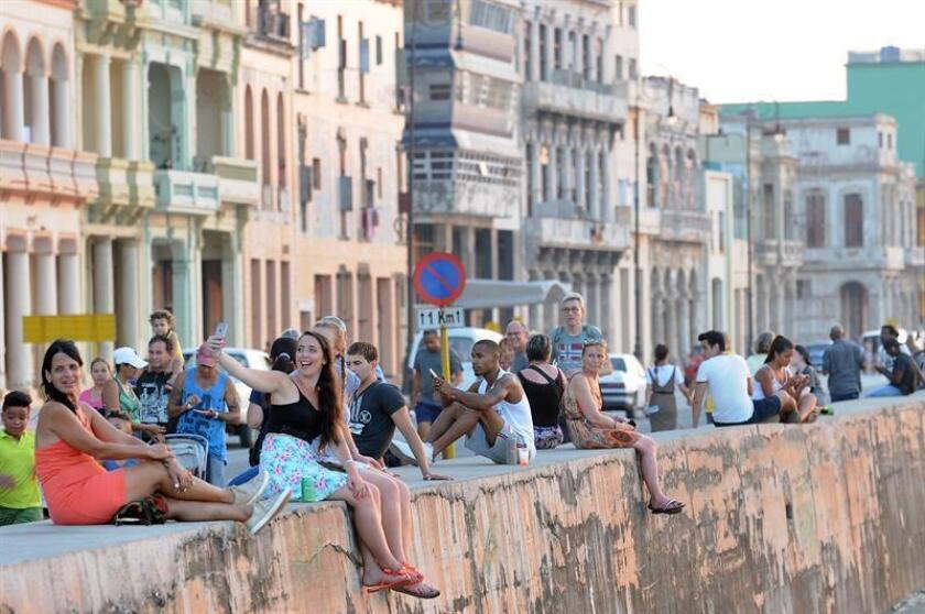 Cubanos y turistas conversan sentados en una zona del malecón, el pasado domingo 04 de marzo del 2019, en La Habana (Cuba). EFE