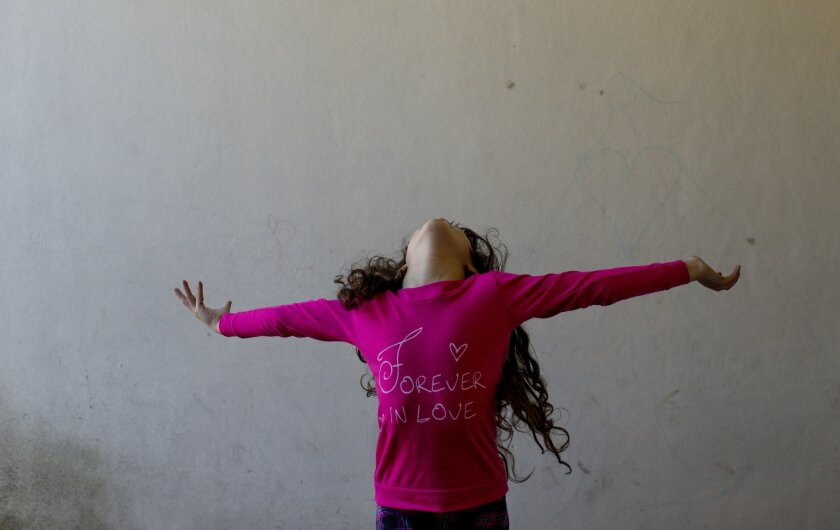 In this Sept. 29, 2015 photo, Luana poses for a picture at her home in Merlo, Argentina. Luana had to fight to be a girl. The 8-year-old was born a boy, and struggled with a world that insisted that this was what she must be. Then, in 2013, she became the youngest person to take advantage of a prog