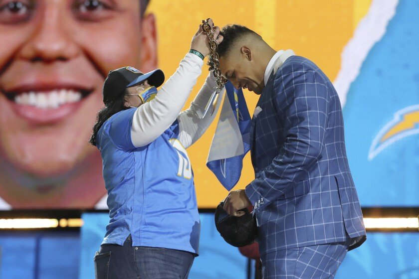 A Chargers fan puts a lightning bolt necklace around the neck of Northwestern tackle Rashawn Slater.