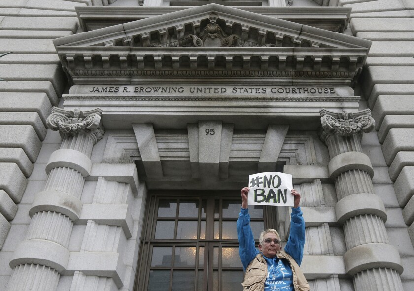 Karen Shore holds up a sign outside of the 9th U.S. Circuit Court of Appeals in San Francisco, Tuesday, Feb. 7, 2017. A panel of appeals court judges reviewing President Donald Trump's travel ban refused to reinstate the order on Thursday.