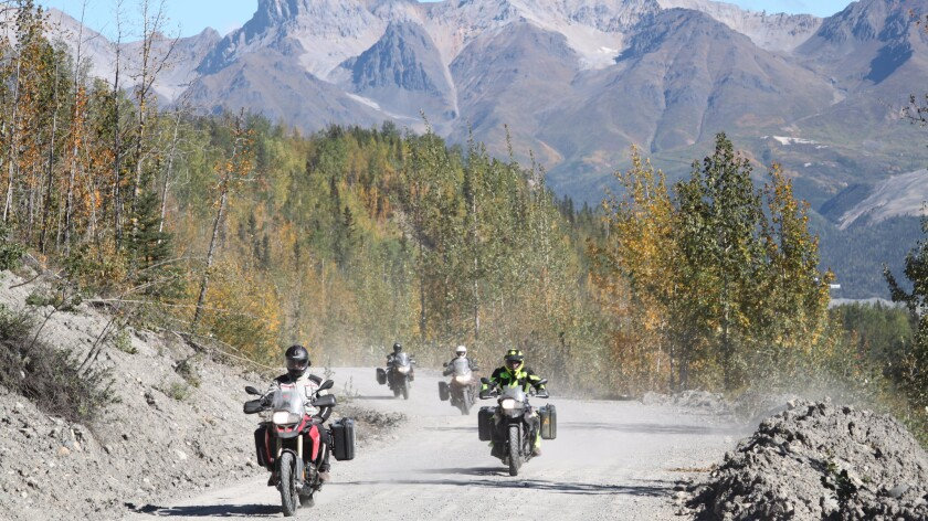 Riders on the Edgerton Highway, which is constructed on top of the old railway that leads to Kennicott Mine in St. Elias National Park. during a MotoQuest motorcycle adventure tour.
