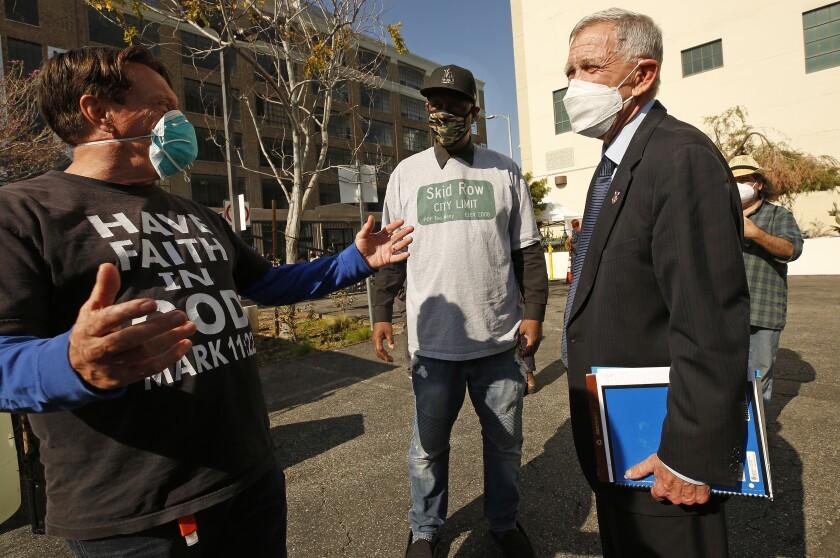 Two men talk with U.S. District Judge David Carter