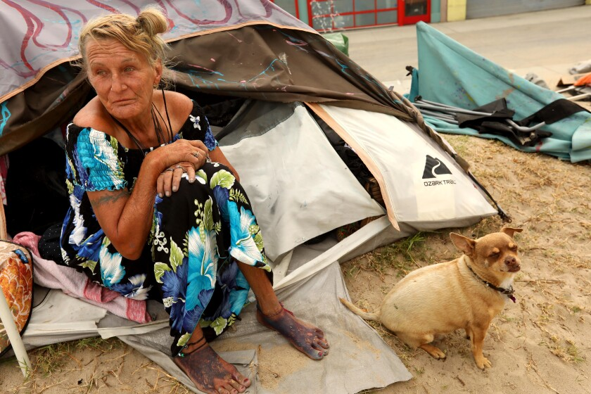 Teresa Robles, 63, and her dog Notcho sit outside their tent along Ocean Front Walk in Venice.