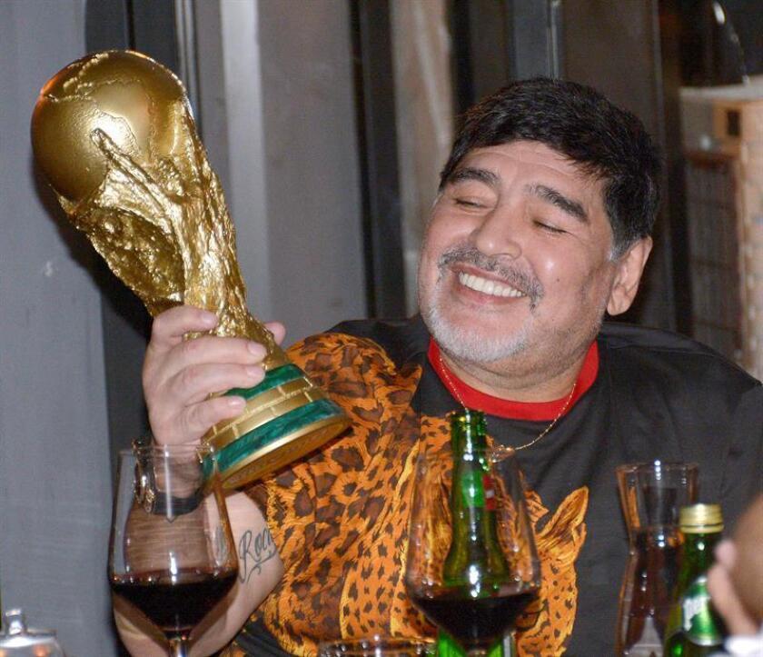 Argentine soccer icon Diego Armando Maradona, now coaching Mexico's Sinaloa Dorados, examines a replica of the World Cup trophy at a dinner in Culiacan, Mexico, on Nov. 6, 2018. EFE-EPA/Juan Carlos Cruz