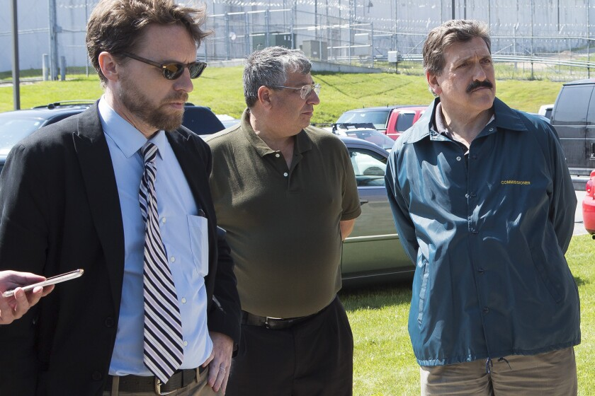 In a Saturday, June 6, 2015 photo, Clinton Correctional Superintendent Steven Racette, center, listens to Gov. Andrew Cuomo speak during a press conference in Dannemora, N.Y.