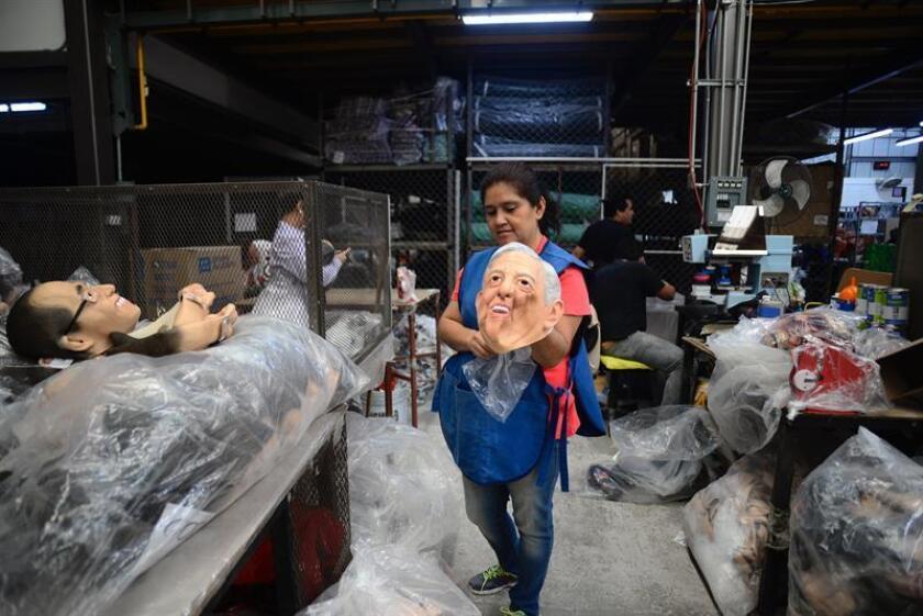 Fotografía del 1 de abril de 2018, de una empleada que muestra máscaras de los candidatos presidenciales en la fábrica que las produce, durante una entrevista con Efe en la ciudad de Cuernavaca (México). EFE
