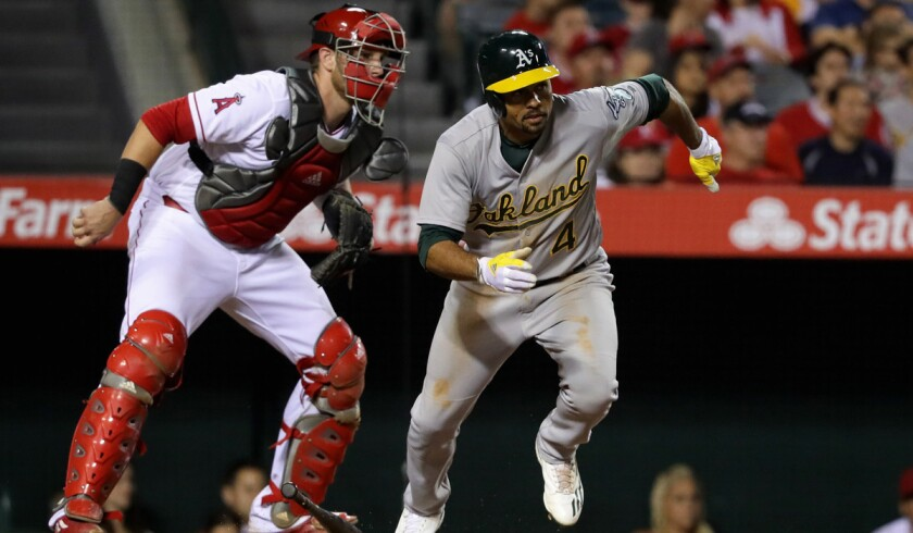 Oakland Athletics' Coco Crisp, right, singles as Angels catcher Jett Bandy looks on during the sixth inning on Saturday at Angel Stadium.