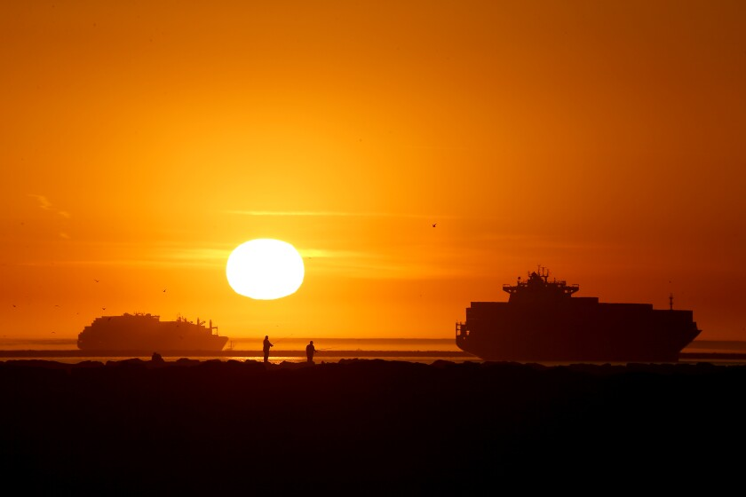 Fishermen set up on the San Gabriel River jetty in front of the setting sun