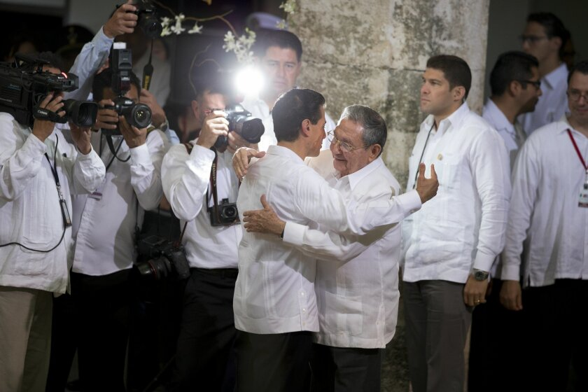 Mexican President Enrique Pena Nieto, center left, hugs Cuban President Raul Castro as Castro arrives for his welcome ceremony at the Yucatan state government palace in Merida, Mexico, Friday, Nov. 6, 2015. Among the agreements to be signed between their nations is a memorandum of understanding to