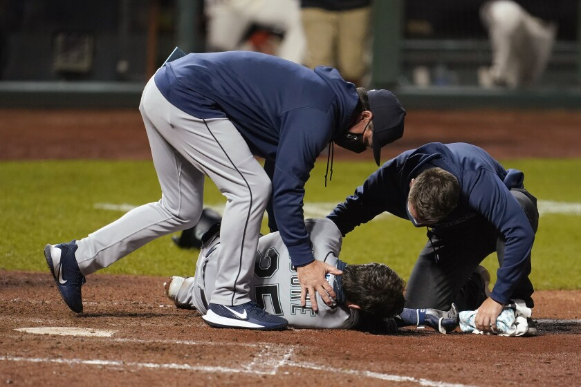 Seattle Mariners manager Scott Servais, left, and a trainer check on Dylan Moore after he was hit by a pitch from San Francisco Giants' Sam Coonrod during the seventh inning of a baseball game in San Francisco, Wednesday, Sept. 16, 2020. (AP Photo/Jeff Chiu)