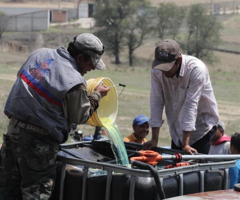Fotografía de varias personas rellenando contenedores con gasolina durante la ordeña clandestina de un ducto de la empresa Petróleos Méxicanos (Pemex). EFE/Archivo