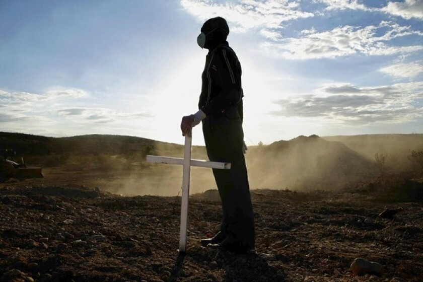 Haitian volunteer Hilaire Polycarpe, 73, holds one of three crosses he painted for communal graves holding 2,500 people north of Port-au-Prince in Titanyen, where the dust was still rising from the burial operation.
