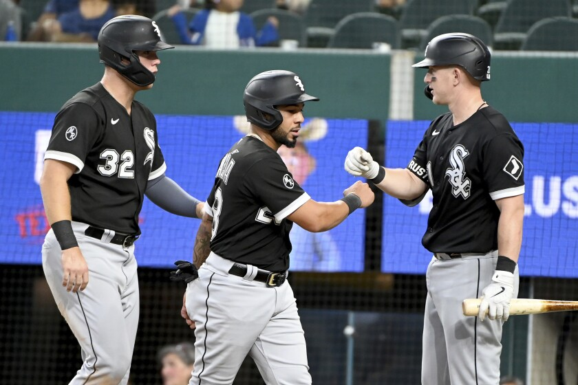 Chicago White Sox' Gavin Sheets (32) and Leury Garcia, center, are congratulated by teammate Zack Collins after scoring runs in the fourth inning during a baseball game against the Texas Rangers in Arlington Texas, Sunday, Sept. 19, 2021. (AP Photo/Matt Strasen)