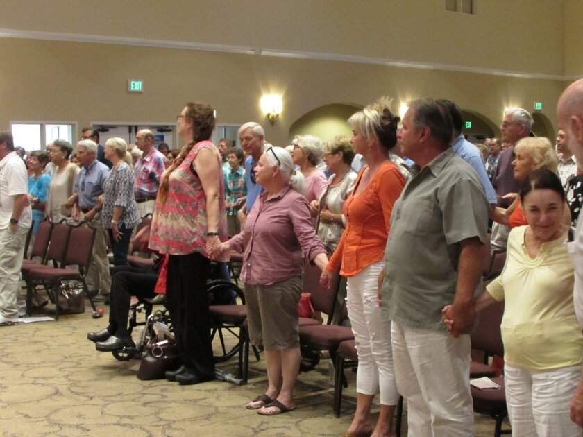 Community members stand and link hands for a rendition of 'We Shall Overcome' Sept. 19 in the Fellowship Hall of La Jolla Presbyterian Church.