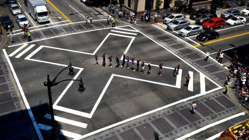 """The cast of """"On Your Feet!"""" participates in a dedication ceremony for a scramble crosswalk at the intersection of Hollywood Boulevard and Vine Street on July 12, 2018."""