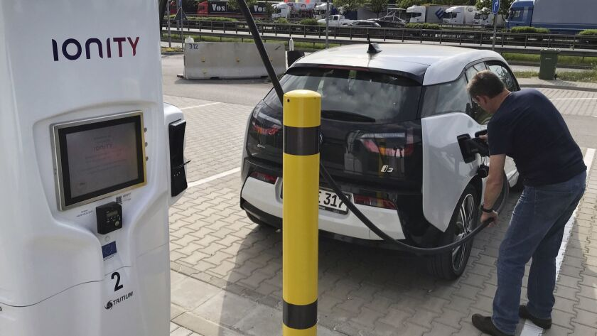 In this Friday, May 11, 2018 photo a man charges his BMW electric vehicle at the rest stop Brohltal