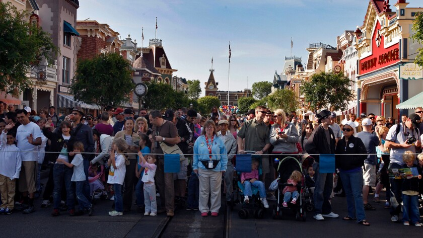 Crowds wait for entry to the Disneyland attractions on Main Street U.S.A. The park is reintroducing its Southern California annual passes at a higher price.