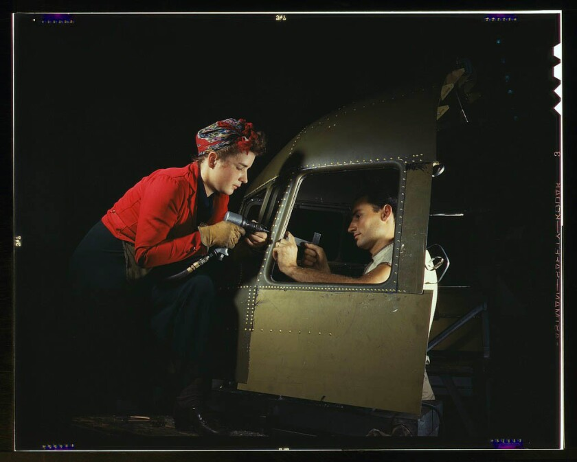 A woman and man work on a C-47 at the Douglas Aircraft Company plant in Long Beach, CA. Oct. 1942.