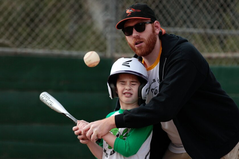 Include Autism Baseball League volunteer Larry Caouette assists Paul Rosenberg, 9, at bat during an adapted baseball game in Rancho Penasquitos Saturday.