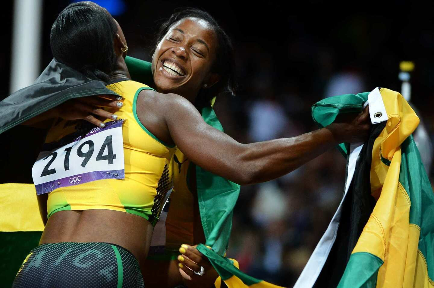 Gold medal winner Shelly-Ann Fraser-Pryce, right, and bronze medal winner Veronica Campbell-Brown embrace after the 100-meter finals. Both are from Jamaica.
