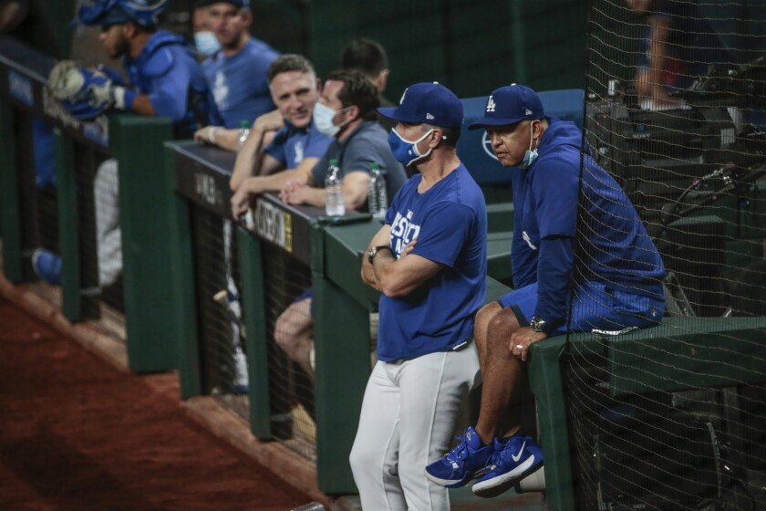 Dodgers manager Dave Roberts and coach Bob Geren watch batting practice the night before Game 1 of the NLCS.