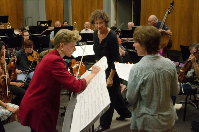 "Violinist Ulli Reiner, left, conductor Ellen Weller and composer Madelyn Byrne confer during a rehearsal of Byrne's ""Decorah Bald Eagle Violin Concerto"" last week with the Palomar Symphony Orchestra at Palomar College."