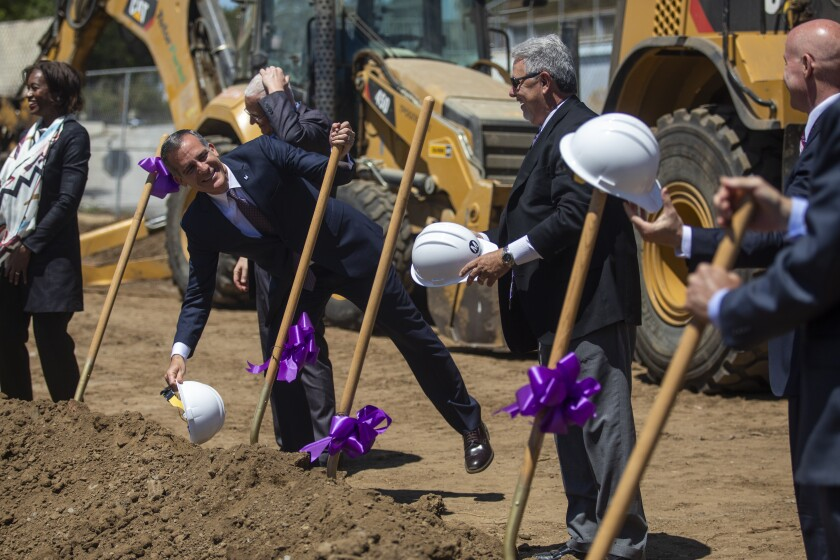 Eric Garcetti grasps the handle of a shovel, one among several stuck in a mound of dirt and decorated with purple ribbon.