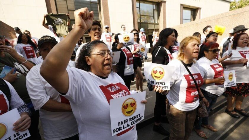 Maria Leon, left, from East Los Angeles joins crowd on steps of County Hall of Administration Tuesday to urge Supervisors to extend a cap rent increases through 2019.