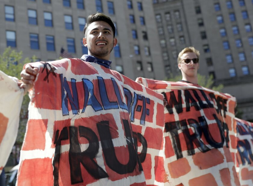 Immigrant rights activists hold up a fabric wall to protest Republican presidential candidate Donald Trump's border wall idea, Wednesday, July 20, 2016, in Cleveland, during the third day of the Republican convention. (AP Photo/Patrick Semansky)