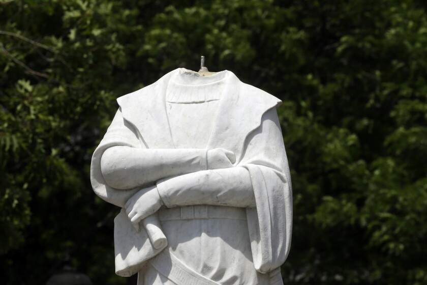 A beheaded Christopher Columbus statue stands in a waterfront park in Boston.