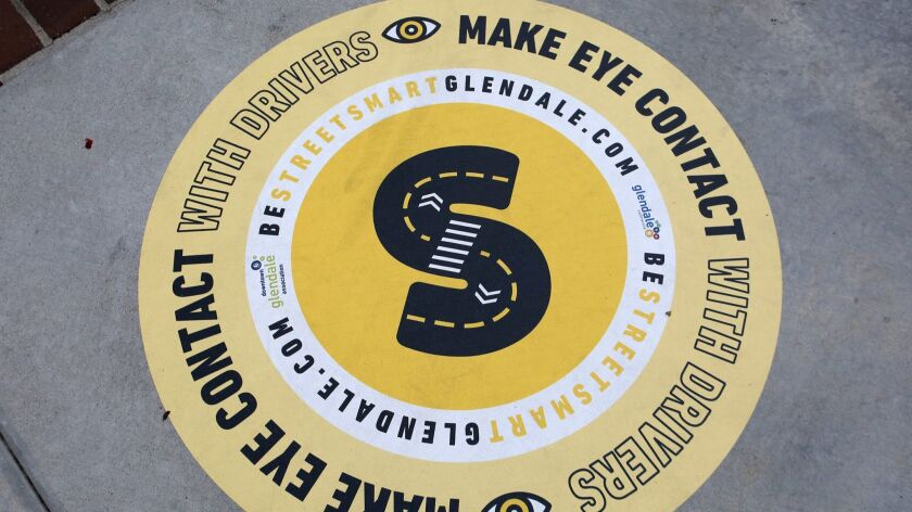 The city of Glendale has placed 60 decals like this one on sidewalks throughout downtown, between Colorado Street and the 134 Freeway. The decals are designed to make pedestrians aware of their surroundings and to make crossing streets safer.