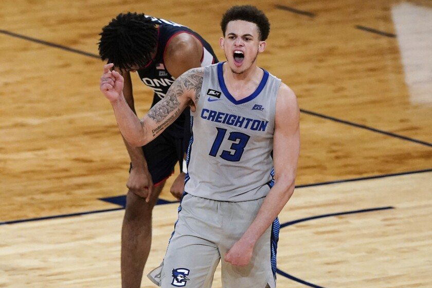 Creighton's Christian Bishop (13) celebrates next to Connecticut's Isaiah Whaley (5) after an NCAA college basketball game in the semifinals in the Big East men's tournament Friday, March 12, 2021, in New York. Creighton won 59-56. (AP Photo/Frank Franklin II)