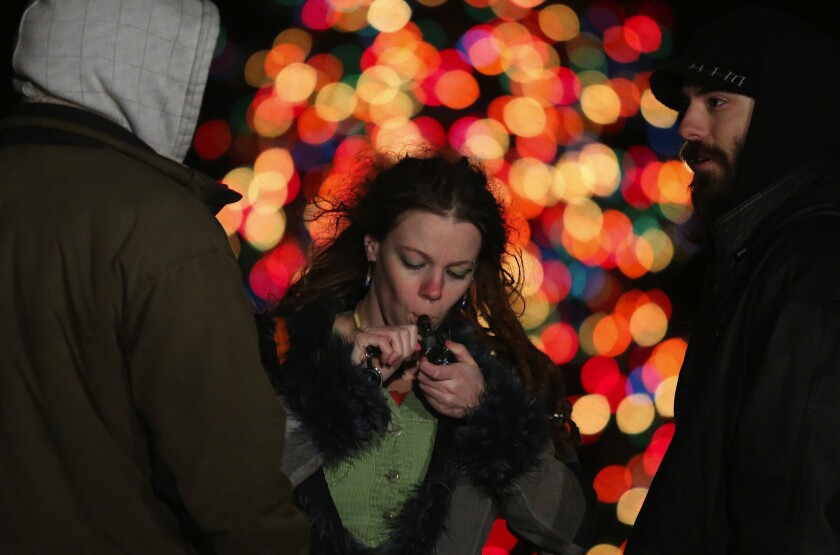 A woman in Seattle lights her pipe as supporters celebrate the legalization of marijuana in Washington state.