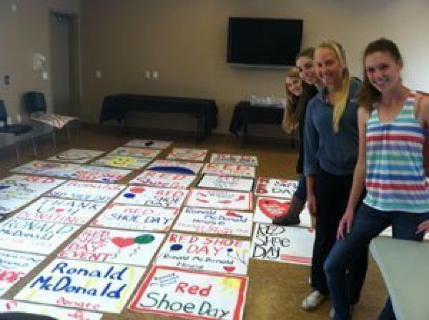 University City High School teens paint posters for the Ronald McDonald House: Delaney Appel, Rebecca McConnell, Anna McSwiggen and Ciara Schnitzer.