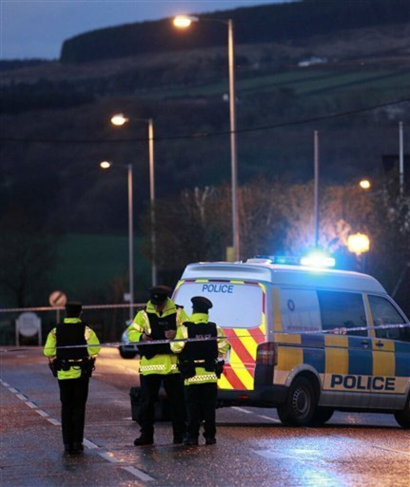 Police Service of Northern Ireland officers secure the area close to where a police officer was killed in a under car bomb at his house in Omagh, Northern Ireland, Saturday, April, 2, 2011. (AP Photo/Peter Morrison)