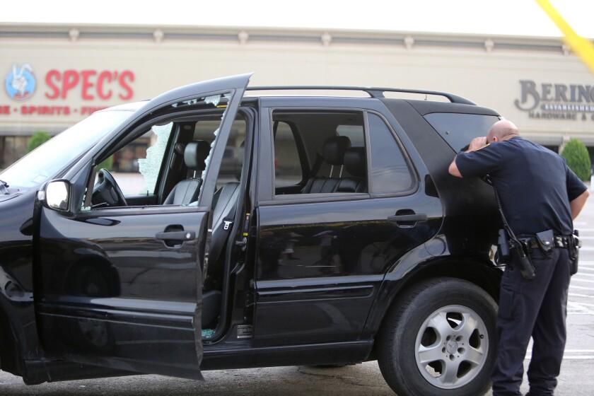Un policía inspecciona un vehículo que recibió disparos cuando pasaba por la calle Law, en Houston, el lunes 26 de septiembre de 2016. Nueve personas resultaron heridas de bala, una de ellas de gravedad, en Houston por un abogado que comenzó a disparar a la gente. La policía mató al agresor. (Mark Mulligan/Houston Chronicle vía AP)
