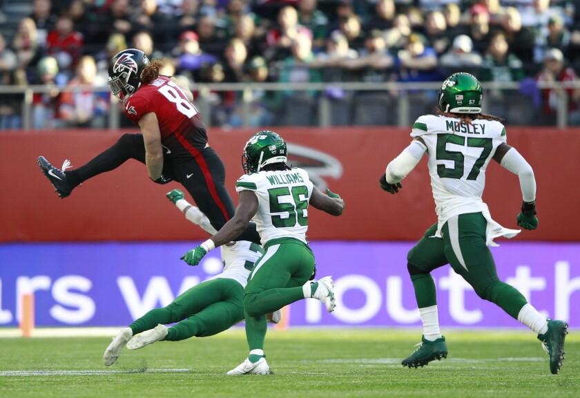 El tight end Hayden Hurst (81), de los Falcons de Atlanta, salta para evitar una tacleada