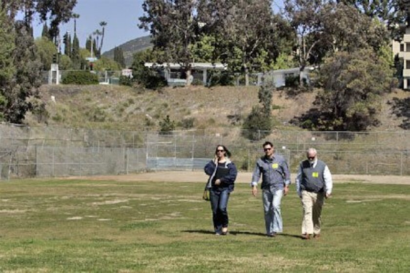 San Diego Unified's Jim Watts (right), accompanied Lisa Hill (left) and Scott Snyder, who work for a company representing ConocoPhillips, as they walked away from a fenced-off area on a ballfield at Patrick Henry High School. (Laura Embry / Union-Tribune)
