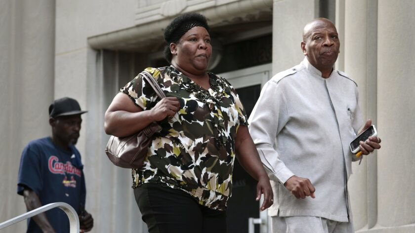 Annie Smith, the mother of Anthony Lamar Smith, enters the Carnahan courthouse with activist Anthony