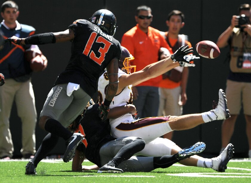 Oklahoma State safety Jordan Sterns, left, watches as Central Michigan wide receiver Jesse Kroll, right, being tackled by Oklahoma State corner back Ramon Richards, bottom, tosses the ball back to Central Michigan wide receiver Cory Willis resulting in a touchdown during the final seconds of an NCA