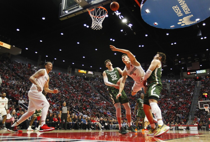 SDSU's Yanni Wetzell is fouled by Colorado State's Nico Carvacho (left) as David Roddy defends.