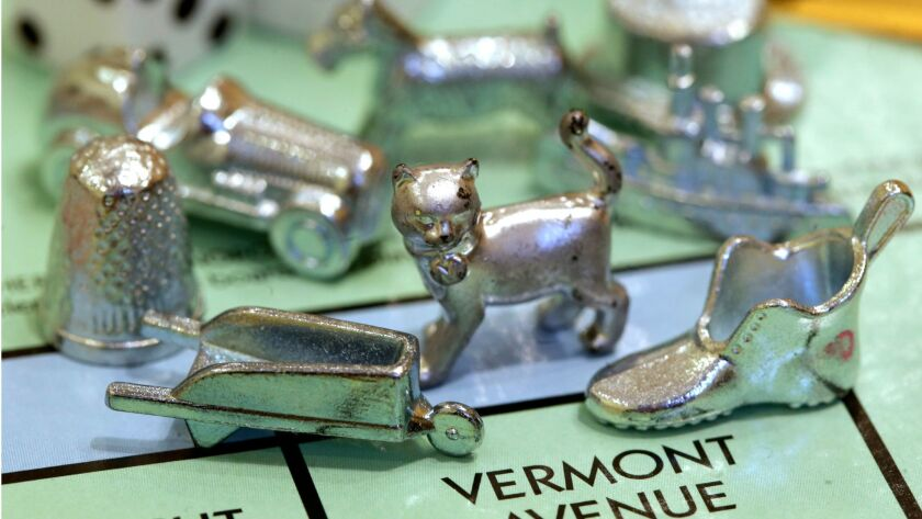 The thimble game piece, left, sits among other Monopoly tokens at Hasbro Inc., headquarters in Pawtucket, R.I.